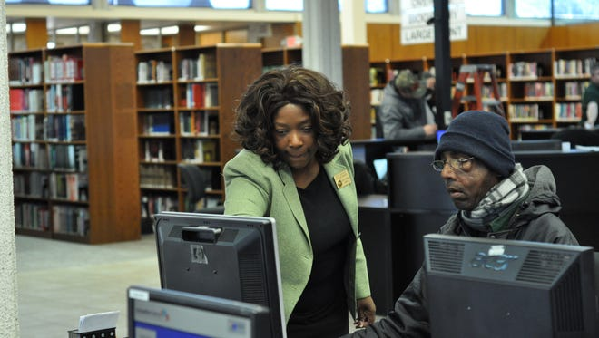 Faith Johnson, reference manager at theRapides Parish Library's Main Library, helps a customer Tuesday, the day the branch reopened after being closed for more than two months for renovations.