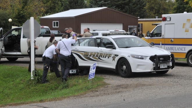 Gold Cross paramedics speak with Kyle Whalen, back of the sheriff's car, after he was taken into custody on Sunday morning. Authorities say Whalen led multiple law enforcement agencies on a pursuit throughout the area before being apprehended near Stearns County Road 137.