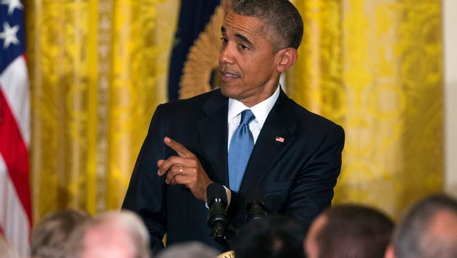 President Barack Obama responds to a heckler as he speaks during a reception to celebrate LGBT Pride Month in the East Room of the White House, on Wednesday, June 24, 2015, in Washington.