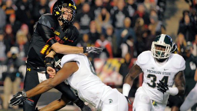 Maryland quarterback C.J. Brown gets hit by a Michigan State defender as he passes for an incompletion during the first quarter Saturday at Byrd Stadium in College Park, Maryland.