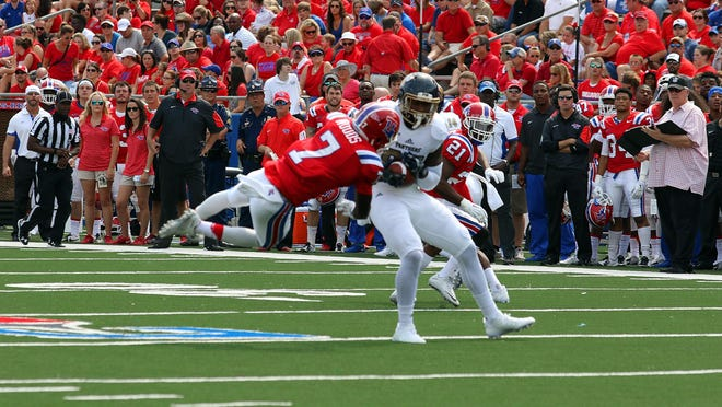 Louisiana Tech safety Xavier Woods leaps to break up a pass against FIU.