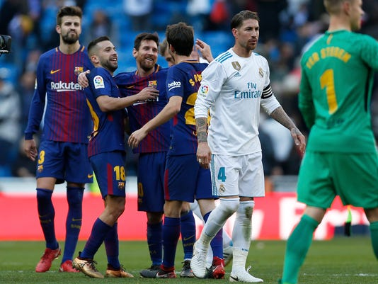 Barcelona's Lionel Messi, 3rd left, celebrates with his teammates at the end of the Spanish La Liga soccer match between Real Madrid and Barcelona at the Santiago Bernabeu stadium in Madrid, Spain, Saturday, Dec. 23, 2017. Barcelona won 3-0. (AP Photo/Francisco Seco)