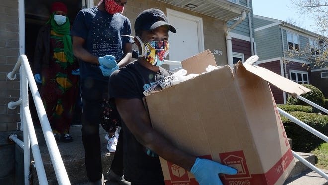 Ibrahim Rashid, 19, carries meals to be delivered to residents in Erie Housing Authority properties on May 12. Behind him is Jafari Verite, also 19. About 150 meals per day are delivered. Funding is provided by the Erie Community Foundation, the Erie Housing Authority and the Minority Community Investment Coalition.