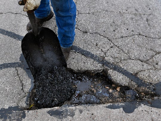 Laramey Sturgeon fills a pothole on North 10th Street with asphalt Tuesday.