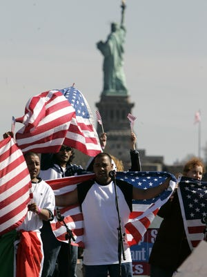 People wave U.S. flags from a stage at Liberty State Park behind the Statue of Liberty during an immigrants rally   in Jersey City, N.J., Monday, April 10, 2006.  Several thousand people rallied to protest sweeping immigration reforms that Congress is considering.    (AP Photo/Mike Derer)