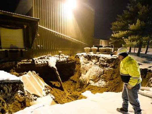 A Pennsylvania American Water employee inspects a large sinkhole that opened up on the property of Philadlephia Mixing Solutions in Palmyra on Sunday, Feb. 10, 2014. The sinkhole caused at least one building to partially collapse. Jeremy Long -- Lebanon Daily News