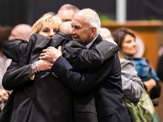 Friends embrace after the memorial service for Ronald