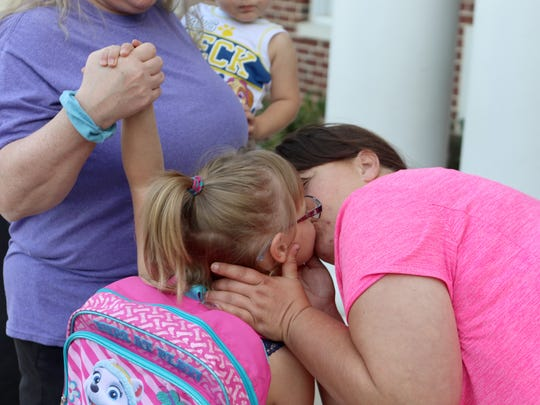 Laurie Wilcutts kisses her daughter, Cheyenne Jarman, on Monday at the J. Ralph McIlvaine Early Childhood Center in Magnolia. It was Jarman's first day of school as a kindergartner.