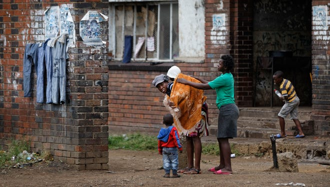 A woman resident assists another to put her baby on her back in the low-income neighborhood of Mbare in Harare, Zimbabwe on Nov. 16, 2017.