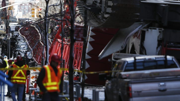 A construction crane lies on a street in downtown Manhattan in New York on February 5, 2016. A giant crane crashed in New York's Tribeca neighborhood Friday, killing one person and injuring two others, a fire department spokesperson said. The crane fell lengthwise along Worth Street, hitting several parked cars but also a vehicle in the middle of the road. / AFP / KENA BETANCUR (Photo credit should read KENA BETANCUR/AFP/Getty Images)