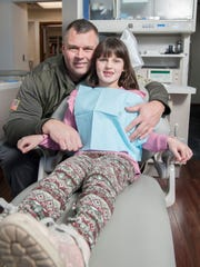 Charlotte Koveloski, 7, sits by her father Kevin Koveloski of West Amwell Township, following a recent follow-up check-up at Monokian Family & Cosmetic Dentistry in Marlton after Charlotte had her tonsils removed in August.  Dr. David Monokian, D.D.S, discovered that Charlotte needed her tonsils removed after she was snoring and not getting good sleep at night.  12.28.17
