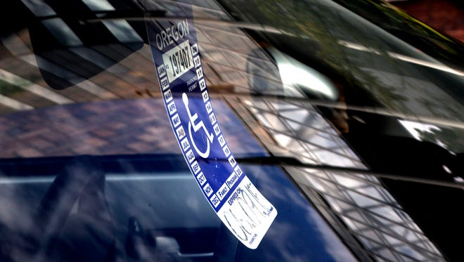 A handicapped parking tag hangs from the rearview mirror of a car parked at a metered parking spot in Portland, Ore., Sept. 3, 2013.