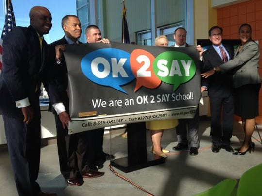 Speakers at a news conference this morning unfurl a banner promoting a new school safety reporting program, called OK2SAY, which allows students and adults to call, text and email tips about school violence.