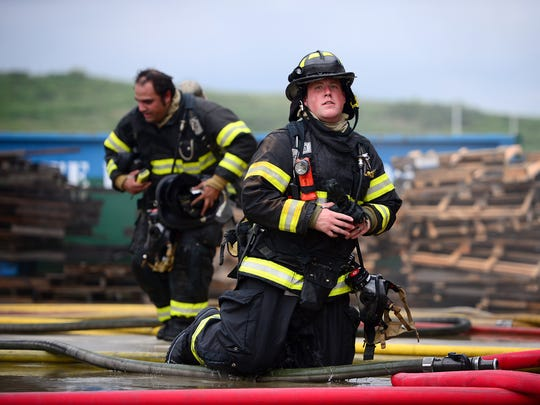 Phillip Padilla, left, and James Wilks, right, work on a fire call at one of the buildings of the Buncombe County Emergency Services Training Facility during the Asheville Fire Department's graduation exercises on Thursday, Aug. 10, 2017.