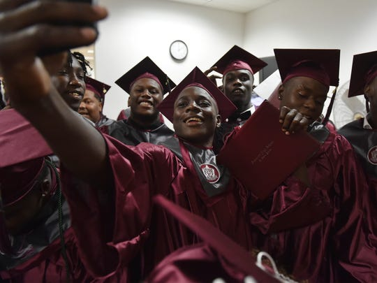 Fort Pierce Westwood High School graduate Cornelius Brown (center) celebrates with a selfie with friends after their Class of 2018 commencement ceremony at the Havert L. Fenn Center on Tuesday, May 22, in Fort Pierce. CQ: Cornelius Brown, Havert L. Fenn