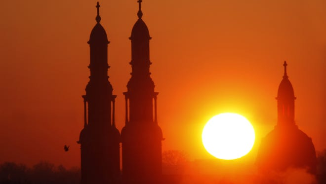 Mother of God Church's twin clock towers and dome bracket a sunrise.