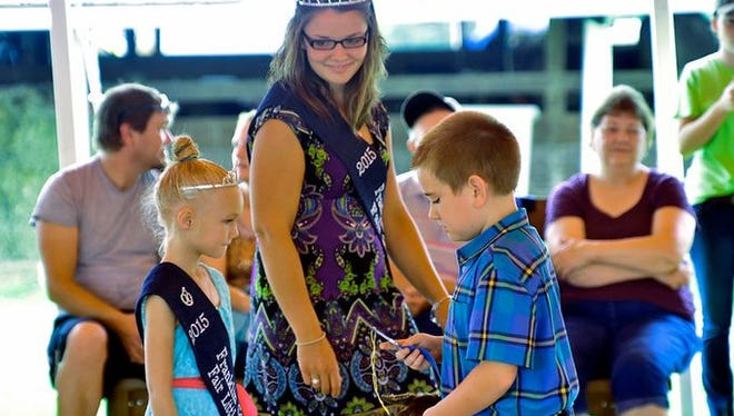 Wesley Reynolds gets a first-place ribbon from 2015 Franklin County Fair Little Miss Morgan Shatzer, left, as 2015 Fair Queen Kayla Hartung looks on, July 8, 2015. The contestants named 2016 Franklin County Fair royalty on Monday, July 11, 2016, will hand out ribbons to contest winners this year, too.