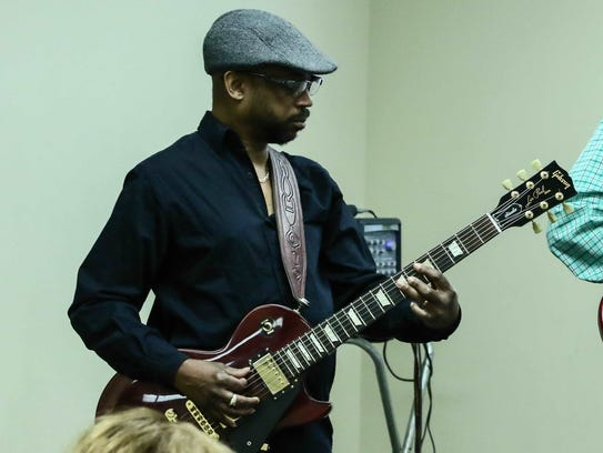 Stroke survivor Lewis Lott performs a guitar solo during
