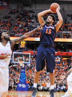 Virginia Cavaliers forward Anthony Gill (13) takes a jump shot with Syracuse Orange forward Rakeem Christmas (25) defending during the first half of a game at the Carrier Dome.