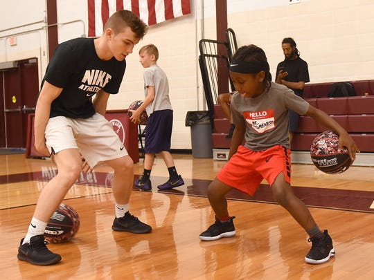Newark High School junior Caleb Nichols works with second-grader Chandler Jackson, 7, on dribbling and ball-handling during the boys basketball 'Cat Camp on Tuesday, June 5, 2018.