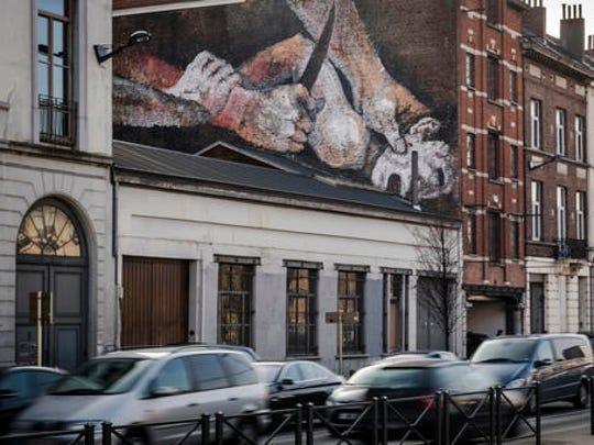A mural of a struggling child with a knife to his neck is painted on the wall of an house in Brussels, Thursday, Jan. 26, 2017. Depicting details from Caravaggio and Dutch Master paintings, an anonymous street artist is the talk of the town and again asks that age-old question about art: how far can it go before it outrages just too much.