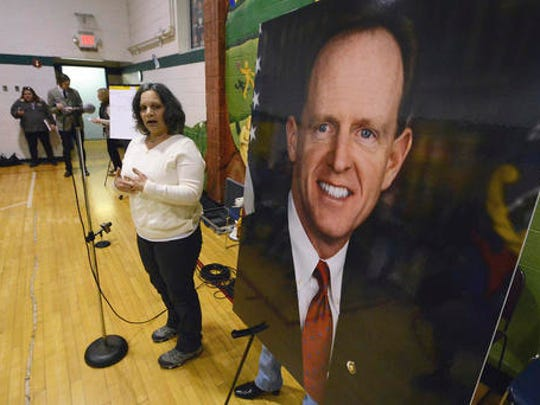 Anna Washick, of Thornhurst, Pa., tells her story regarding health care next to a large photograph of Sen. Pat Toomey, R-Pa., at the United Neighborhood Center in Scranton, Pa., Tuesday, Feb. 21, 2017. Toomey was invited to speak at the town hall, but did not attend.