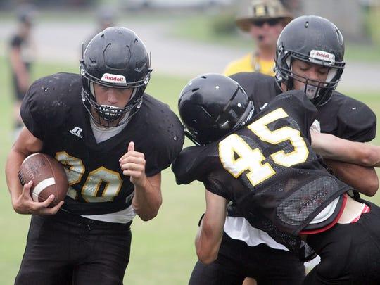 Left, Hendersonville's Nate Hancock rushes in practice
