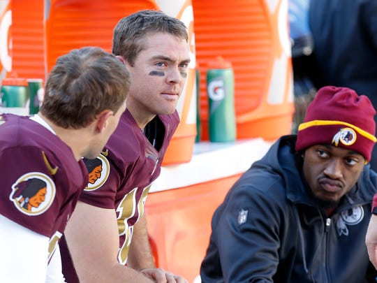 Washington QB Colt McCoy (M) sits on the bench with Kirk Cousins (L) and Robert Griffin III (R) against the Titans in the third quarter at FedEx Field.