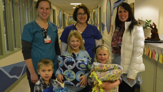 Melissa Buckmaster, back right, and her three children - in front from left, Nolan, Emily and Abigail - donated tie blankets they made to the Jim and Gerry Christoph Pediatric Care Unit at Bellin Hospital in Green Bay on Thursday. Bellin registered nurses Chelsea Prefontaine, in back from left, and Jenny Heyduk accepted the fleece blankets that will be given to sick patients in the unit.