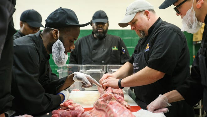 David Faison, left, watches as chef Tom Craft instructs culinary students at the Delaware Food Bank in Newark on Thursday. Low-income participants are taught job skills to help them land a job. Delaware lawmakers are wrestling with how to deal with addressing poverty.