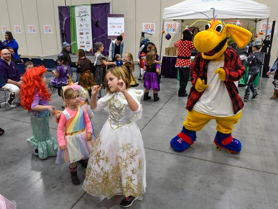 Children dance to the Hokey Pokey with mascots during