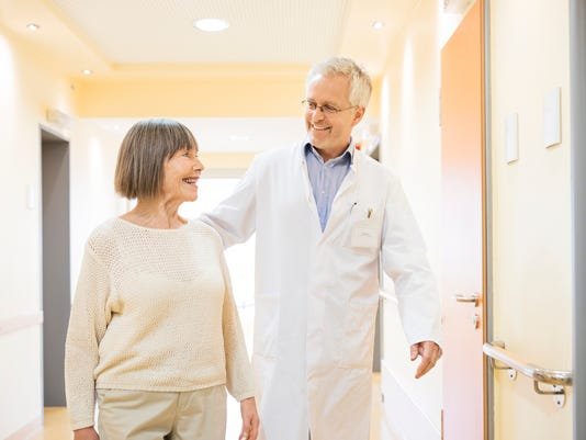 Doctor and senior patient talking in corridor