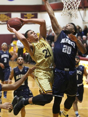 St. Thomas Aquinas' Justin Reyes shoots under pressure from Mercy's K.J. Rose during their game at STAC Feb. 16, 2016. Reyes had 20 points in the 79-44 win, STAC's 15th win in a row.