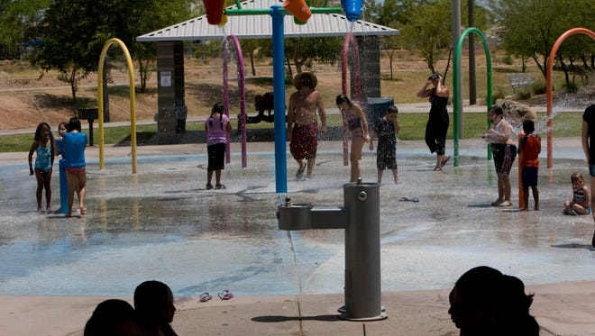 Kids play in the water fountain while parents keep an eye at their children at the splash pad at Goodyear Community Park.