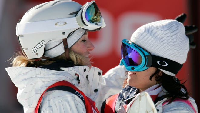 USA's women's snowboard silver medalist Gretchen Bleiler (left) hugs 2002 Salt Lake Olympic women's halfpipe gold medalist USA's Kelly Clark while waiting for her score on her second run down the halfpipe during the womens finals scoring a 44.4 to capture silver medal.