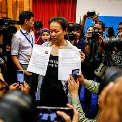 The wife of a missing Flight 370 passenger shows her husband's picture to reporters in Putrajaya, Malaysia, on Jan. 29, 2015.