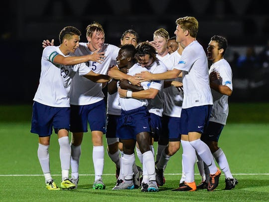 Monmouth University players surround Anderson Asiedu (center) after he scored a goal last season for the Hawks.