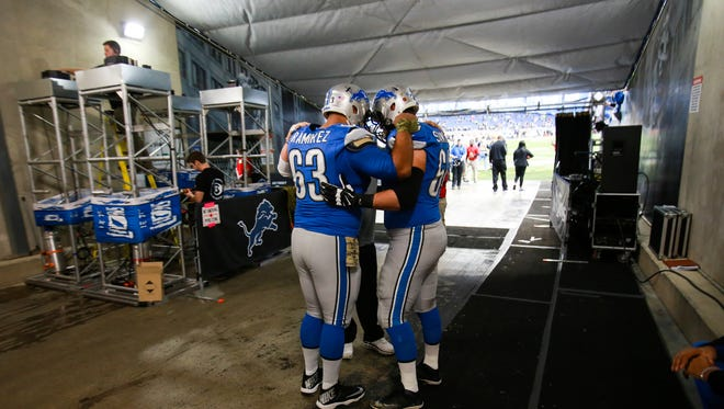 The Lions' Manny Ramirez and Travis Swanson embrace in the tunnel before the win over the Raiders Sunday at Ford Field.