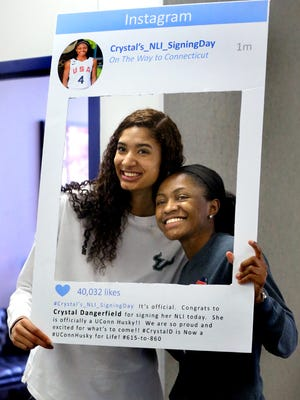 Jazz Bond, left, who signed with USF and Crystal Dangerfield, who signed with UConn get a picture taken in a homemade Instagram sign made by Dangerfield's mother Davonna Dangerfied, during signing day at Blackman, on Wednesday Nov. 11, 2015.