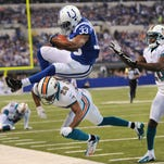 Colts running back Vic Ballard gets flipped into the air as he is hit by Dolphins Nolan Carroll as he leaped for the first down at Lucas Oil Stadium on Nov. 4, 2012.
