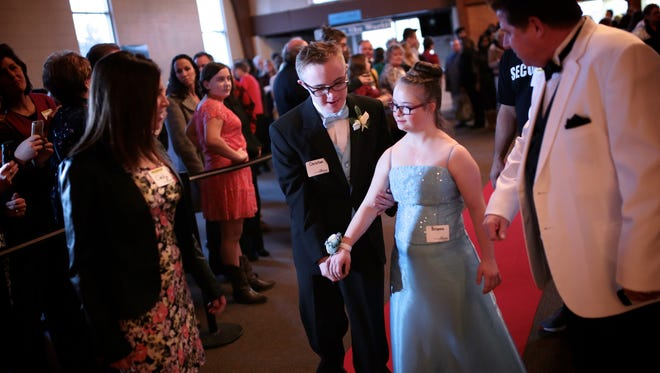 Christian Houlihan, center left, 15, of Grosse Pointe holds the hand of Brianna Taggerty, 15, of Grosse Pointe as they walk the down the red carpet during Night to Shine at Warren Woods Baptist Church on Friday, Feb. 12, 2016, in Warren, MI. About 200 churches nationwide host Night To Shine proms for people with special needs. The event is sponsored by the Tim Tebow Foundation.