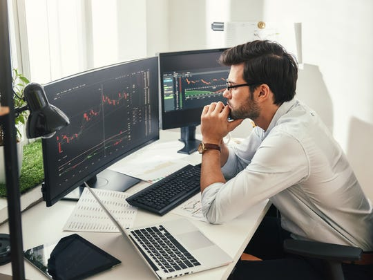 Investor sitting in front of computer with stock charts.