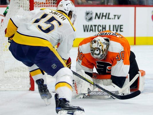 Nashville Predators' Craig Smith, left, looks to Philadelphia Flyers' Michal Neuvirth, who covers up the puck during the first period of an NHL hockey game Thursday, Oct. 19, 2017, in Philadelphia. (AP Photo/Tom Mihalek)