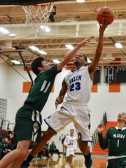Salem senior Cameron Grace (23) goes up for a layup against a Novi defender during Wednesday's Class A district matchup.