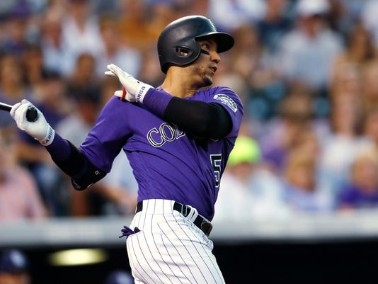 Colorado Rockies' Carlos Gonzalez watches his two-run double off San Diego Padres relief pitcher Phil Maton during the fifth inning of a baseball game Tuesday, July 18, 2017, in Denver. The Rockies won 9-7. (AP Photo/David Zalubowski)