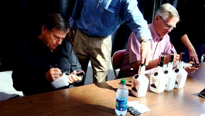 Tom Jurich, left, and Maker's Maker's Bill Samuels sign bottles Wednesday at the KFC Yum! Center.