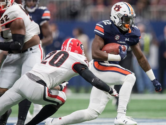 Auburn wide receiver Eli Stove (12) carries against Georgia defensive back J.R. Reed (20) in first half action of the SEC Championship Game at Mercedes-Benz Stadium in Atlanta, Ga. on Saturday December 2, 2017. (Mickey Welsh / Montgomery Advertiser)
