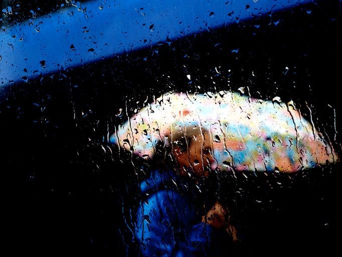 A pedestrian stays dry beneath their umbrella while