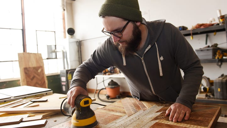 Brad Wall, 25, of Wall Woodworking, sands a tabletop inside his Russell Center studio Tuesday morning.