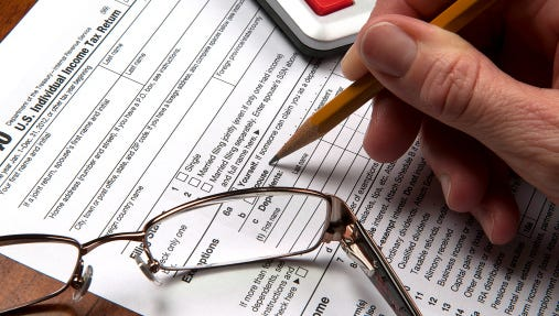 United States tax form with hand sharpened pencil calculator glasses.